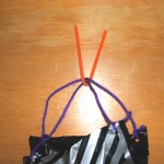 Tie string through holes then twist pipe cleaner around center of strings.