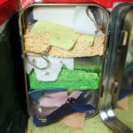 This Altoids tin closet features sponge shelves, and hangers made with packaging wire.