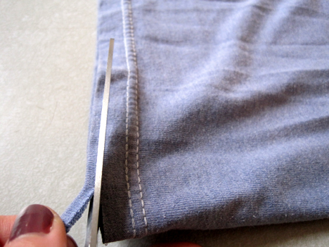 Cut along the bottom hem of the shirt under the stitched seam. If you trim under the stiching the shirt will not loose its shape.