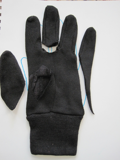 Cut the gloves according to the pattern. This is an example of how each glove would be cut. I left a little more of the thumb on so that it can make a rounded nose.